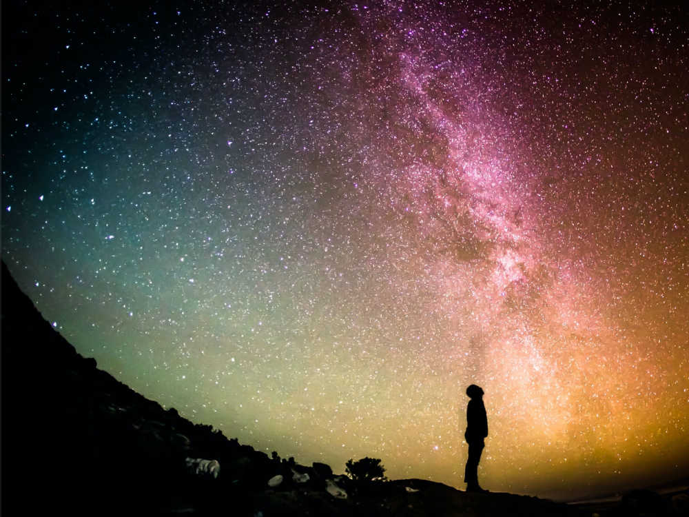 Man standing at night staring at a magical sky